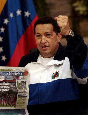 FILE -- IN a July 4, 2011 file photo Venezuela's President Hugo Chavez raises a fist as he holds a copy of a Venezuelan newspaper at the Maiquetia Airport near Caracas, Venezuela.  Chavez is using Twitter as a tool to govern remotely while he undergoes cancer treatment in Cuba.   (AP Photo/Ismael Francisco, Prensa Latina)