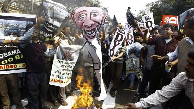 Activist from AIDSO burn a cut-out depicting U.S.President Barack Obama during a protest against his visit to India, in Kolkata