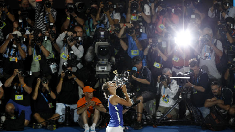 Victoria Azarenka of Belarus kisses the trophy during the awarding ceremony, after defeating Maria Sharapova of Russia in their women's singles final at the Australian Open tennis championship, in Melbourne, Australia, Saturday, Jan. 28, 2012. (AP Photo/Aaron Favila)