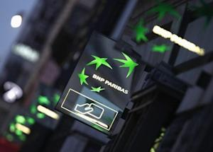 Illuminated signs light up at twilight outside the headquarters of the BNP Paribas bank in Paris