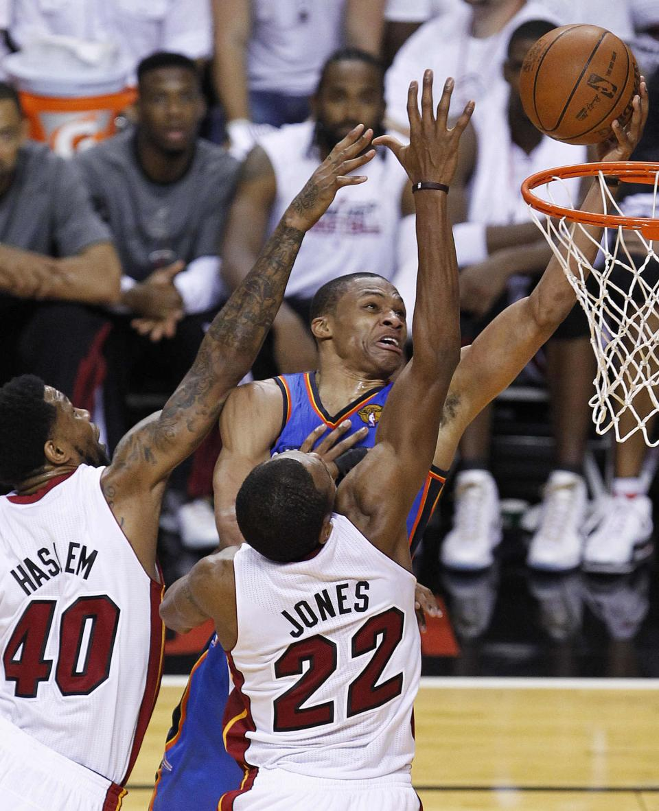 Oklahoma City Thunder point guard Russell Westbrook (0) shoots against Miami Heat power forward Udonis Haslem (40) and small forward James Jones during the second half at Game 4 of the NBA Finals basketball series, Tuesday, June 19, 2012, in Miami.  (AP Photo/Wilfredo Lee)