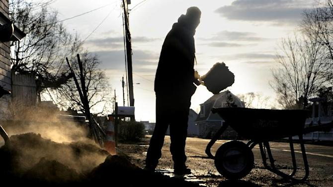 In this Tuesday, Dec. 4, 2012 photo, a landscaper loads mulch into a wheelbarrow at a beachfront home in Fairfield, Conn.  The national economy is expected to absorb the blow from Sandy with little long-term damage, but in the short term, at least, Sandy is introducing dramatic booms and busts across the Northeast. The effects vary widely across industries, bringing banner years for some while pushing others toward economic ruin. (AP Photo/Jessica Hill)