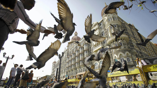 A man feeds pigeons outside the Taj Mahal hotel, one of the targets of the 2008 terror attacks in Mumbai, India, Wednesday, Nov. 21, 2012. India executed the lone surviving Pakistani gunman from the 2008 terror attack on Mumbai early Wednesday, providing Indians much-needed closure over the three-day rampage that shook the nation's core and deepened enmity with neighbor Pakistan.  (AP Photo/Rafiq Maqbool)