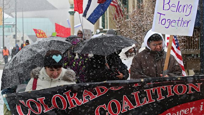 Protesters brave the cold and snow as they march from the Capitol to a park in Denver on Wednesday, May 1, 2013. About 200 people gathered at the Capitol for immigration reform. The May Day rallies carry a special sense of urgency this year, two weeks after a bipartisan group of senators introduced a bill that would bring many of the estimated 11 million living in the U.S. illegally out of the shadows.  Colorado's rally comes just after the governor signed a bill allowing students in the country illegally to pay in-state tuition at state colleges and universities, ending a 10-year political battle.(AP Photo/Ed Andrieski)