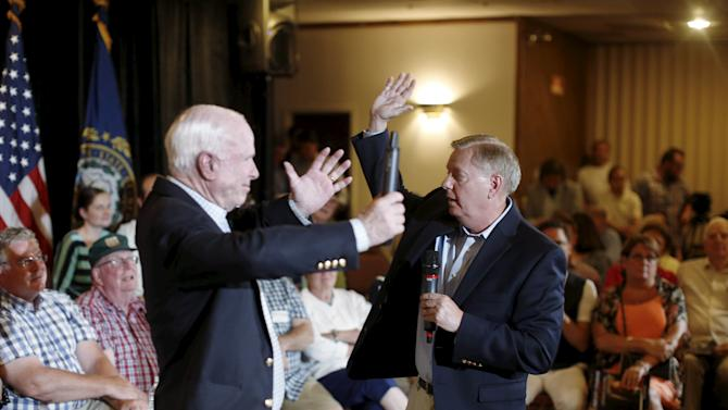 South Carolina Senator and U.S. Republican presidential candidate Graham gestures with Arizona Senator and 2008 Republican presidential nominee McCain at a campaign town hall event in Manchester