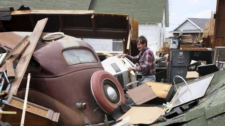 Gary Gladwin works to clear debris from his destroyed garage which held his 1937 Chevrolet Sunday, April 15, 2012, after a tornado moved through Thurman, Iowa Saturday evening. He hopes to find a new top for the car, which was damaged by a downed tree limb. Fremont County Emergency Management Director Mike Crecelius said about 75 percent of the 250-person town was destroyed. (AP Photo/The Des Moines Register, Mary Chind)  NO SALES, NO MAGS, MANDATORY CREDIT
