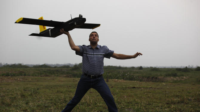 Remo Peduzzi, managing director of ResearchDrones LLC Switzerland prepares to fly an unmanned aircraft or drone at the Kaziranga National Park at Kaziranga in Assam state, India, Monday, April 8, 2013. Wildlife authorities used drones on Monday for aerial surveillance of the sprawling natural game park in northeastern India to protect the one-horned rhinoceros from armed poachers. The drones will be flown at regular intervals to prevent rampant poaching in the park located in the remote Indian state of Assam. The drones are equipped with cameras and will be monitored by security guards, who find it difficult to guard the whole 480-square kilometer (185-square mile) reserve. (AP Photo/Anupam Nath)