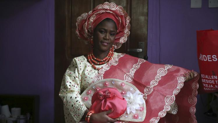 Sunlola Ogungbadero, dressed in traditional attire, poses for a photograph before the start of her traditional wedding in Surulere district, Nigeria's Lagos