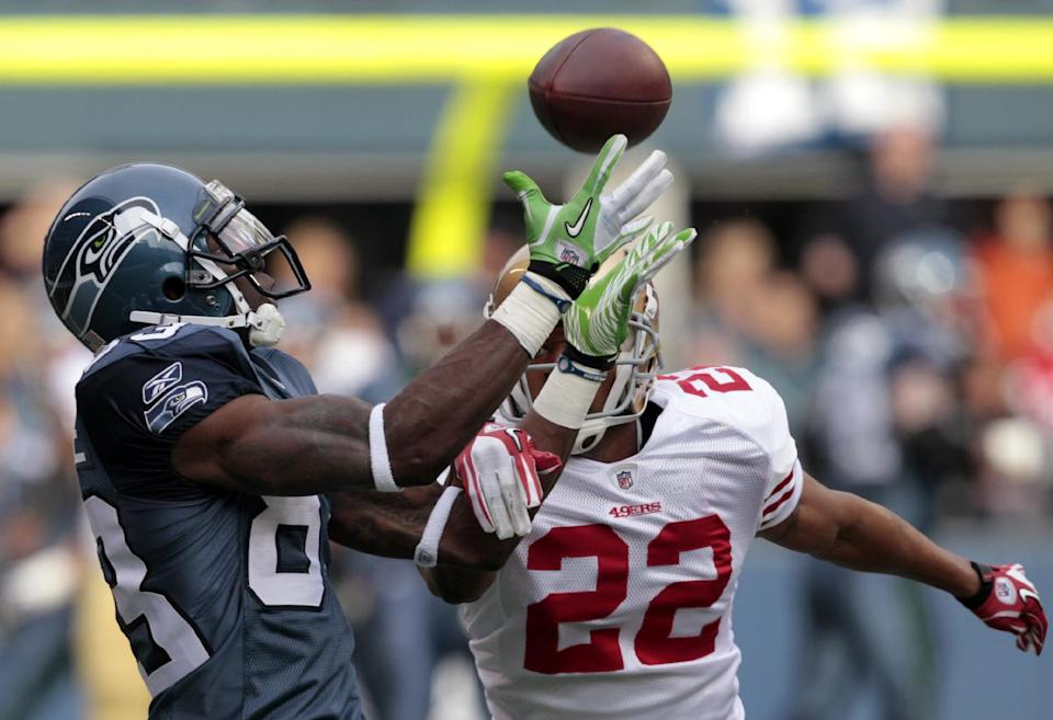 Seattle Seahawks'  Ricardo Lockette, left, catches a 44-yard pass as  San Francisco 49ers'  Carlos Rogers defends in the first half of an NFL football game Saturday, Dec. 24, 2011, in Seattle. (AP Photo/Elaine Thompson)