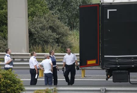 French policemen and a truck driver inspect the trailer of a truck searching for migrants as lorries wait on a road which leads to the Channel Tunnel terminal in Coquelles near Calais