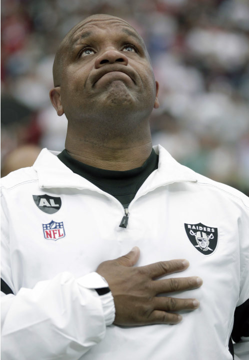 Oakland Raiders head coach Hue Jackson looks up during a tribute to late Raiders owner Al Davis before the NFL football game against the Houston Texans Sunday, Oct. 9, 2011, in Houston. Davis passed a