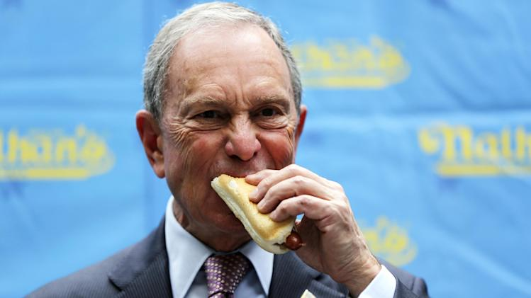 New York City mayor Michael Bloomberg eats a hot dog during the official weigh-in