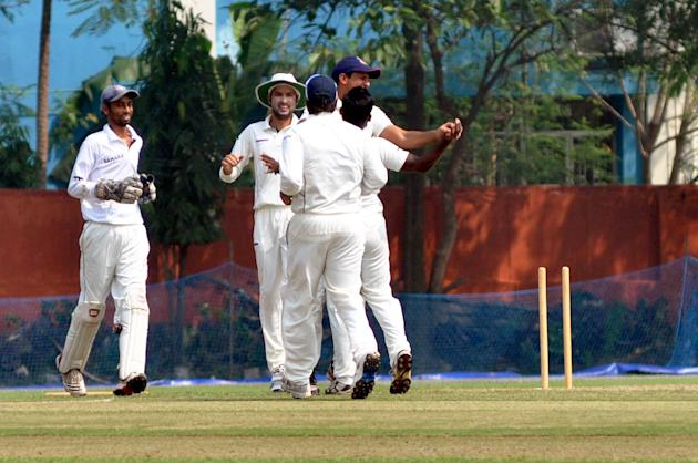 Uttar Pradesh XI players celebrate the dismissal of Chris Gayle during practice match between Uttar Pradesh Cricket Association XI and West Indies at the Jadavpur University Ground in Kolkata on Oct.3