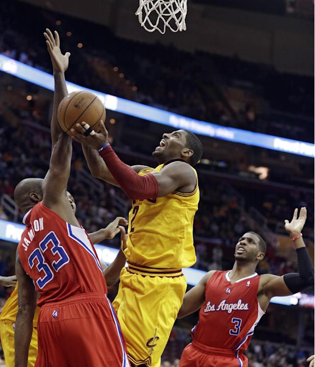 Cleveland Cavaliers' Kyrie Irving, center, jumps to the basket between Los Angeles Clippers' Antawn Jamison, left, and Chris Paul, right, during the fourth quarter of an NBA basketball game on
