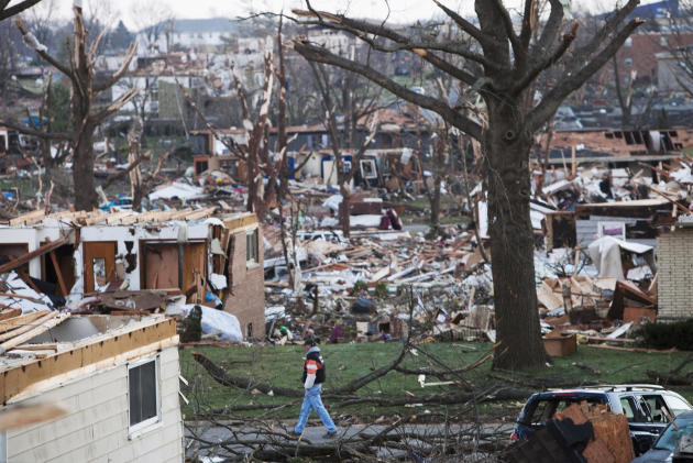 FILE - In this Nov. 18, 2013 file photo, a man walks through what is left of a neighborhood in Washington, Ill., a day after a tornado ripped through the central Illinois town. Tornado sirens were tes