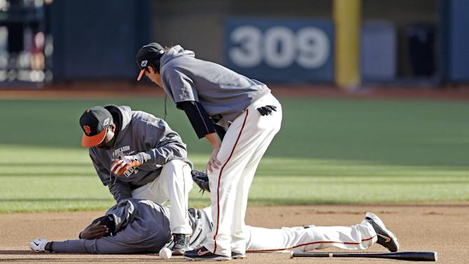 San Francisco Giants first base coach Roberto Kelly lies on the ground after getting hit with a ball during a practice session for baseball's National League championship series Saturday, Oct. 13, 2012, in San Francisco. The Cardinals play the San Francisco Giants in Game 1 of the NLCS on Sunday. (AP Photo/Mark Humphrey)