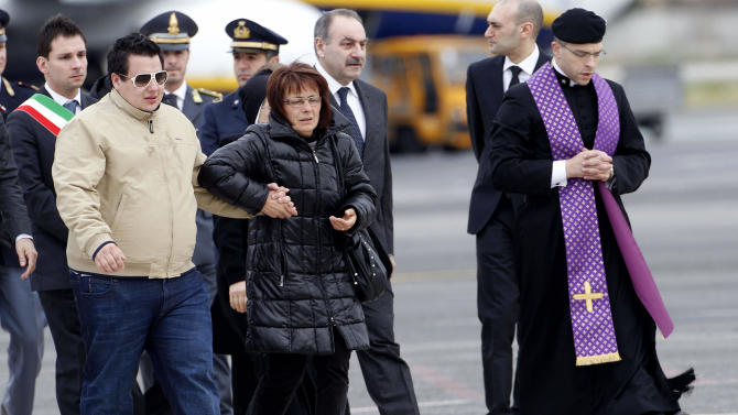 The son of Franco Lamolinara, Mattia left, and his sister Angela walk towards the coffin of their relative upon its arrival at Rome's Ciampino military airport Saturday, March 10, 2012. An Italian Air Force jet has flown to Rome with the body of an Italian hostage slain in Nigeria during a botched British-Nigerian rescue attempt. The body of Franco Lamolinara was to be brought to a morgue for autopsy. The jet arrived Saturday at Rome's Ciampino military airport, where officers were stood at attention in a sign of respect. Lamolinara, an engineer, was working in Nigeria when he was kidnapped along with a British colleague, in May. (AP Photo/Pier Paolo Cito)