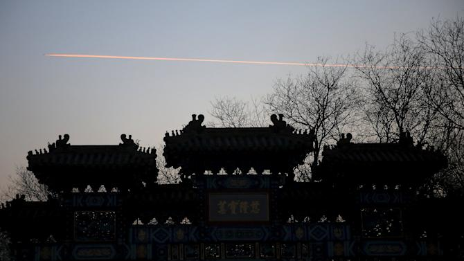 A plane is seen from Yonghegong Lama Temple as it flies over Beijing on the first day of the Lunar New Year of the Monkey in Beijing