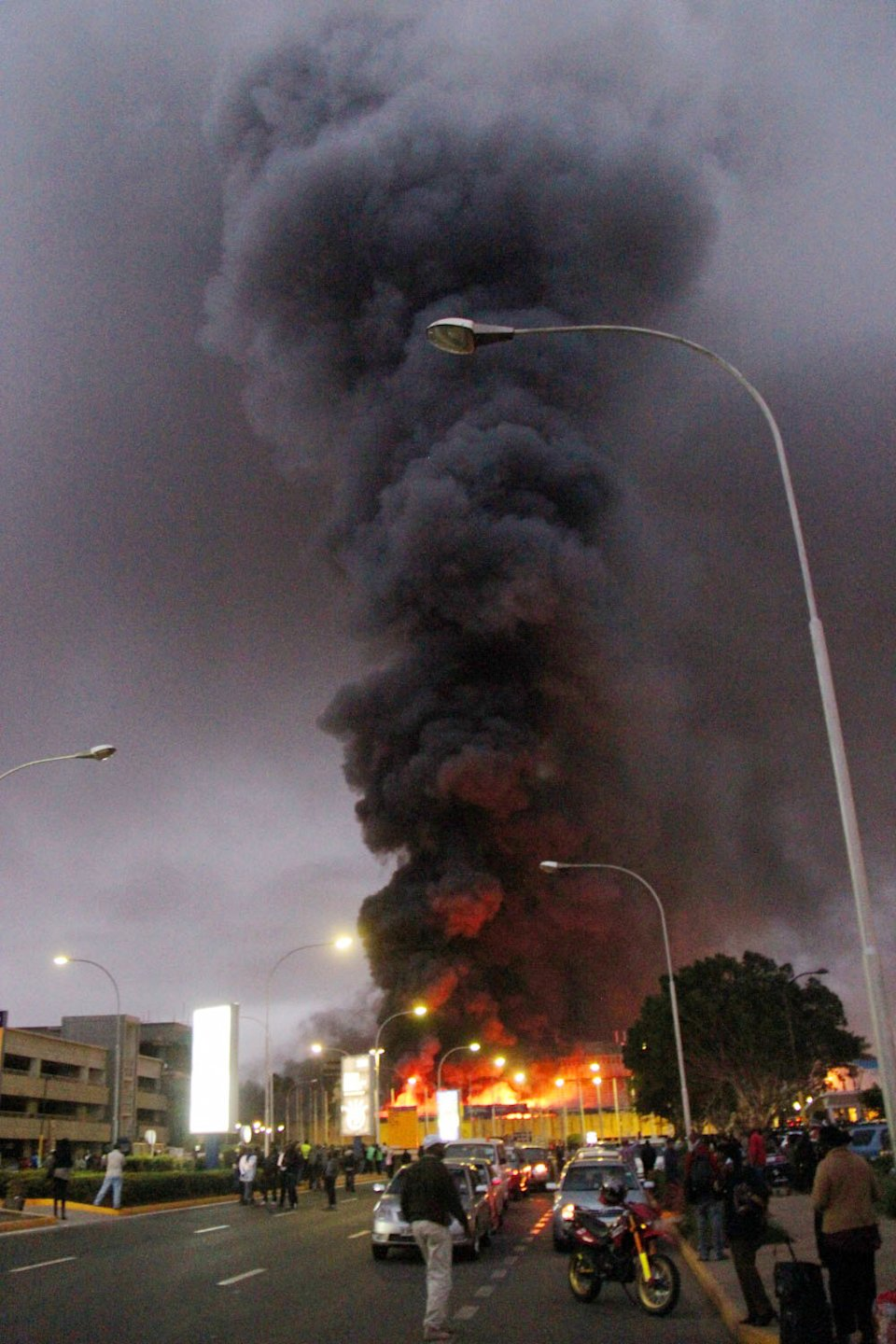 People watch dense black smoke billowing from the Jomo Kenyatta International Airport in Nairobi, Kenya, early Wednesday, Aug. 7, 2013. Firefighters are battling a large blaze raging at Kenya's main international airport. The Kenya Airports Authority said Wednesday that the airport has been closed until further notice so that emergency teams can battle the fire. (AP Photo/Kyodo News) JAPAN OUT, MANDATORY CREDIT