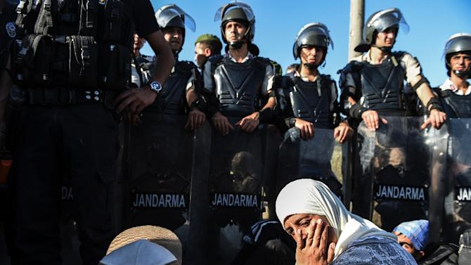 Syian refugees sit in front of a police barricade as they march along the highway towards the Turkish-Greek border at Edirne on September 18, 2015