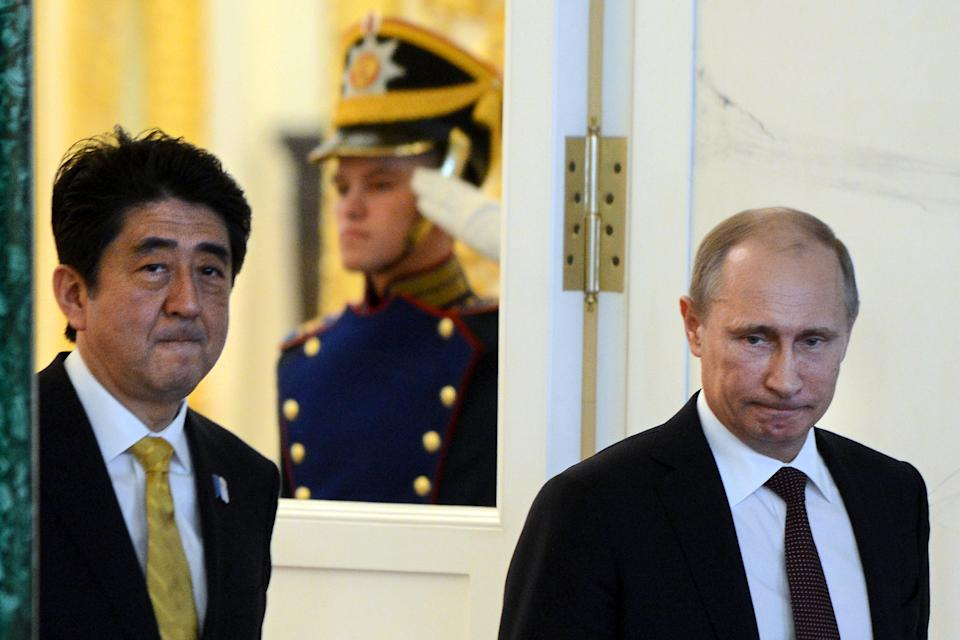 Russian President Vladimir Putin and Japanese Prime Minister Shinzo Abe, left, arrive for a news conference in Moscow's Kremlin on Monday, April 29, 2013. Abe is in Russia on an official visit. (AP Photo/Kirill Kudryavtsev, Pool)