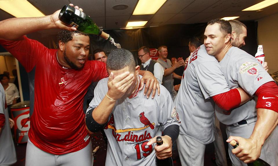From left to right, St. Louis Cardinals' Victor Marte, Jon Jay, Chris Carpenter and Carlos Beltran celebrate in the locker room after defeating the Atlanta Braves 6-3 in the National League wild card playoff baseball game on Friday, Oct. 5, 2012, in Atlanta. (AP Photo/John Bazemore)
