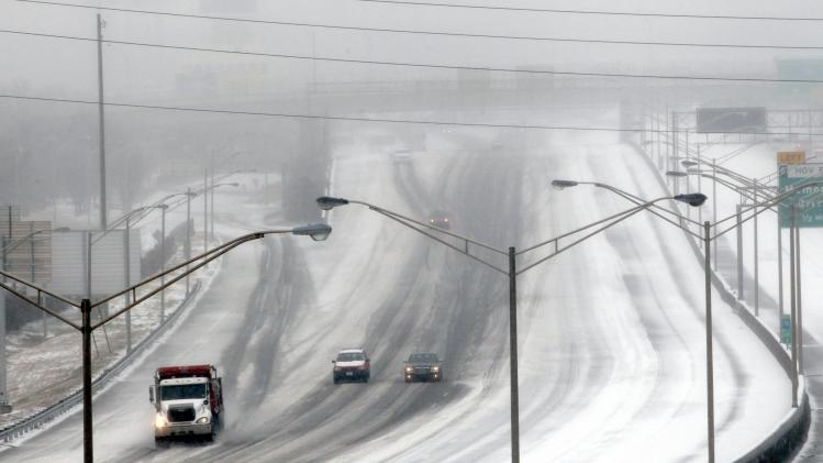A sand truck dumps salt and sand on a downtown expressway as drivers follow behind during an ice storm in Atlanta
