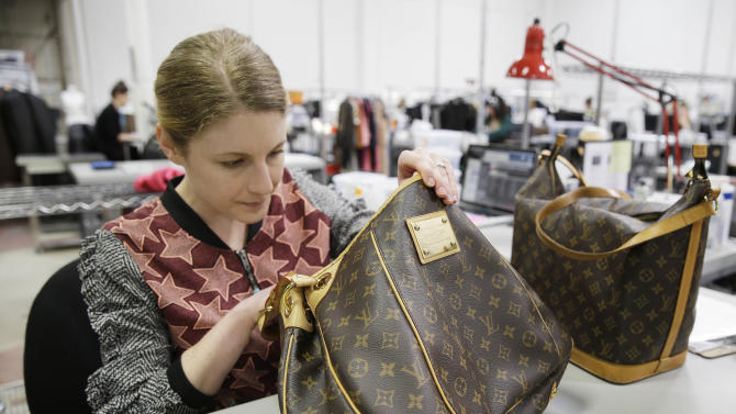 In this photo taken Wednesday, April 9, 2014, Jenna Starr inspects a pair of Louis Vuitton handbags to authenticate them and make sure they meet brand standards at the headquarters of The RealReal in San Francisco. An explosion of resale online sites from RealReal to Chairish that allows shoppers to easily trade in their gently used top brand handbags, furniture and gadgets for cash is changing the way Americans buy. The ease of reselling their possessions allows consumers to keep refreshing their wardrobes and homes without feeling guilty. (AP Photo/Eric Risberg)