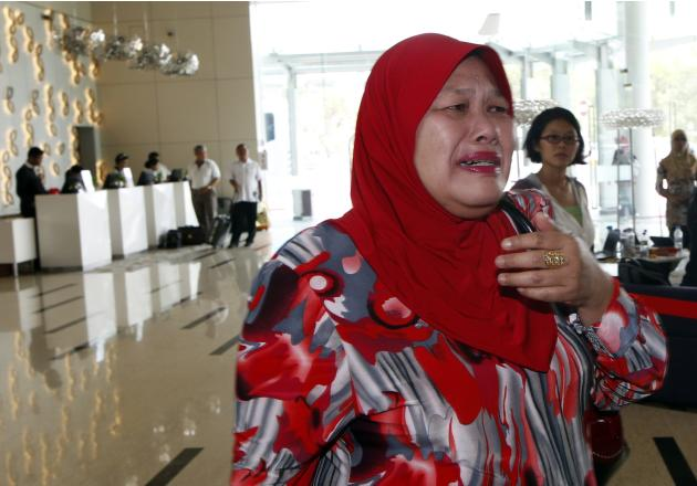 Family member of a passenger on missing Malaysia Airlines MH370 plane cries as she enters hotel where family members of those aboard flight are being put up, in Putrajaya