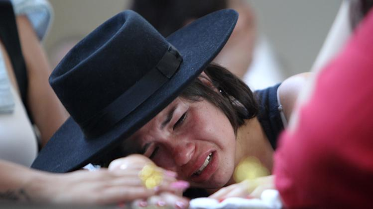 A woman cries over the coffin of  her boyfriend at a gymnasium where bodies were brought for identification in Santa Maria city, Rio Grande do Sul state, Brazil, Sunday, Jan. 27, 2013. They were both at the Kiss nightclub when flames raced through the crowded club in southern Brazil early Sunday, killing more than 230 people as panicked partygoers gasped for breath in the smoke-filled air, stampeding toward a single exit partially blocked by those already dead. (AP Photo/Nabor Goulart)