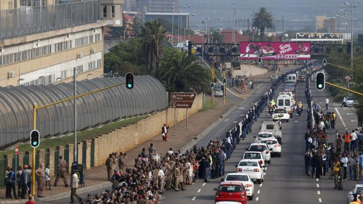 Prison wardens and members of public watch as procession carrying coffin of former President Mandela makes its way past Pretoria Central Prison
