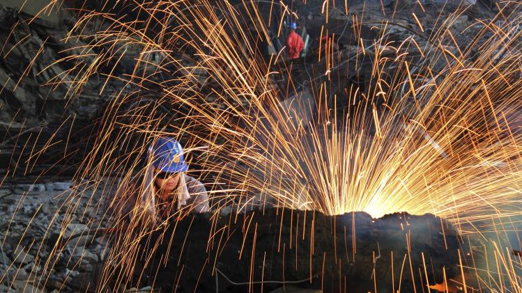 A labourer cuts scrap steel at a factory of Dongbei Special Steel Group Co., Ltd., in Dalian