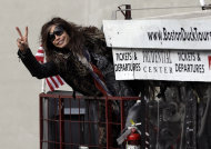 Aerosmith's Steven Tyler gestures after climbing aboard a duck boat which transported the band Monday, Nov. 5, 2012 to Boston's Allston neighborhood where they gave a free concert. Aerosmith performed in front of the building which was their home in the early 1970's. (AP Photo/Elise Amendola)