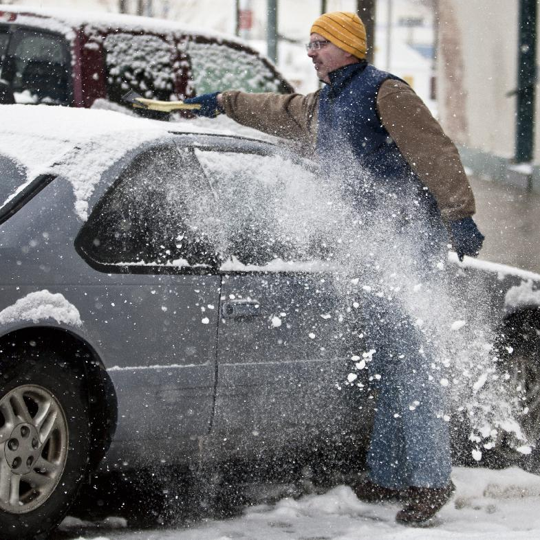 Laramie resident John Waggener brushes the snow from the roof of his car after enjoying dinner at a downtown restaurant in Laramie, Wyo., Tuesday, April 9, 2013. (AP Photo/Laramie Boomerang, Jeremy Martin)