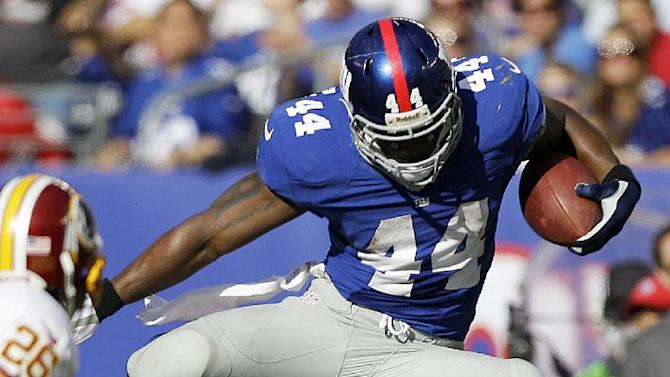 New York Giants running back Ahmad Bradshaw, top, leaps over Washington Redskins free safety Madieu Williams (41) for a first down during the second half of an NFL football game on Sunday, Oct. 21, 2012, in East Rutherford, N.J. The Giants won the game 27-23. (AP Photo/Kathy Willens)