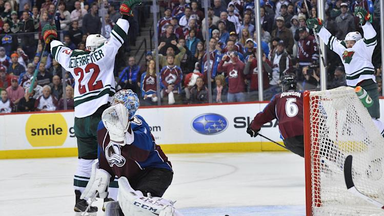 The puck bounces out of the net after Colorado Avalanche goalie Semyon Varlamov, second from left, of Russia lets the winning goal slip past off the stick of Minnesota Wild right wing Nino Niederreiter (22) of Switzerland in the overtime period during Game 7 of an NHL hockey first-round playoff series on Wednesday, April 30, 2014, in Denver. Minnesota won 5-4 to win the series