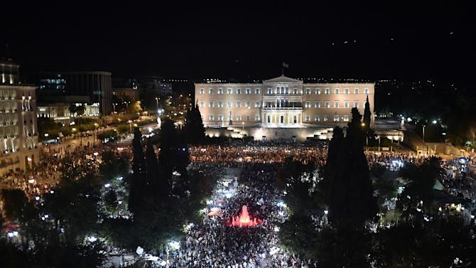People gather in front of the Greek parliament in Athens on July 5, 2015, after early results showed those who rejected further austerity measures in a crucial bailout referendum were poised to win