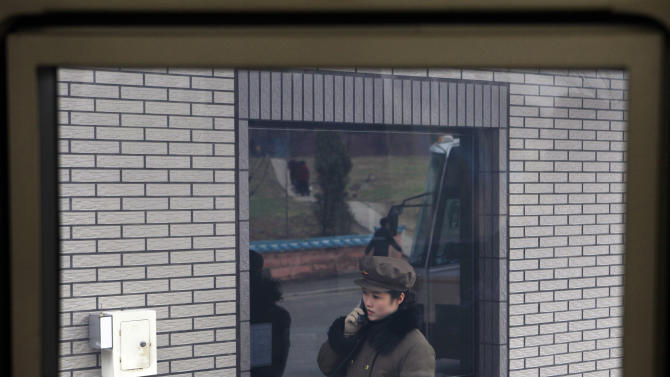 A female North Korean guard calls on the phone at the entrance to the Hana Music Information Center in Pyongyang, North Korea, Thursday, April 12, 2012. (AP Photo/Ng Han Guan)
