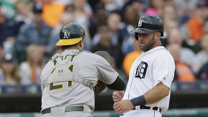Detroit Tigers' Tyler Collins is tagged out by Oakland Athletics catcher Stephen Vogt on a rundown during the third inning of a baseball game, Tuesday, June 2, 2015, in Detroit. (AP Photo/Carlos Osorio)