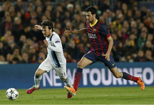 Manchester City's David Silva, left tries to get past Barcelona's Sergio Busquets during a Champions League, round of 16, second leg, soccer match between FC Barcelona and Manchester City at t