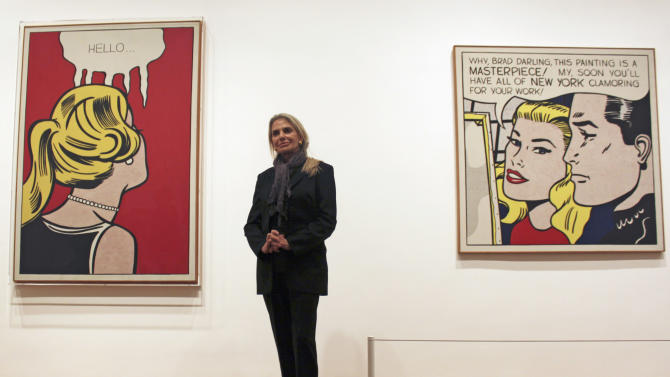 """In this May 11, 2012 photo, Dorothy Lichtenstein, widow of pop artist Roy Lichtenstein, stands between his artworks """"Cold Shoulder,"""" left, and """"Masterpiece"""" at the Art Institute of Chicago. The museum has opened """"Roy Lichtenstein: A Retrospective,"""" which runs through Sept. 3 before traveling to Washington, London and Paris. (AP Photo/Caryn Rousseau)"""