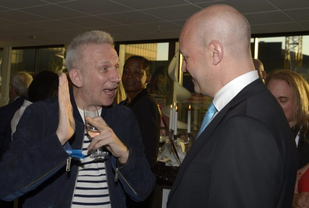 French fashion designer Gaultier speaks to Swedish PM Reinfeldt during the arrival party of the 2013 Eurovision Song Contest final in Malmo