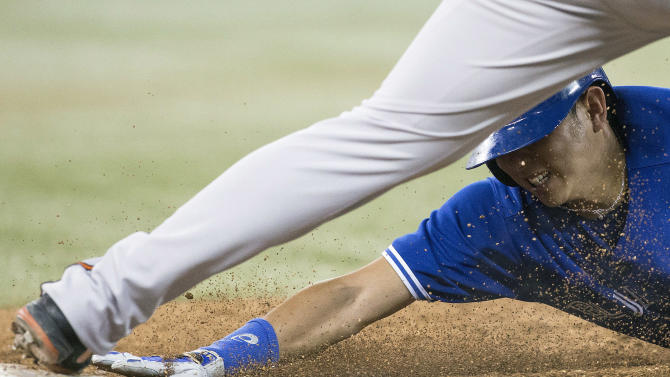 Toronto Blue Jays' Munenori Kawasaki, bottom, is forced out at first on a double play by Baltimore Orioles' Travis Ishikawa during the fifth inning of a baseball game in Toronto, Saturday June 22, 2013. (AP Photo/the Canadian Press, Chris Young)