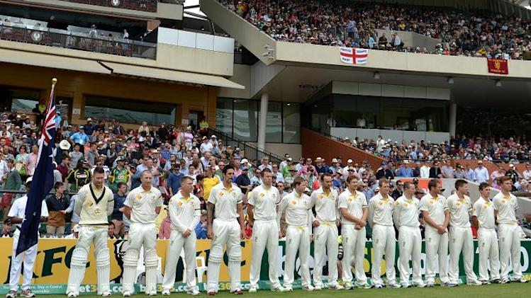 Australian cricketers observe a minute's silence to mark the passsing of former South African president Nelson Mandela on the second day of the second Ashes cricket Test match between England and Australia in Adelaide on December 6, 2013
