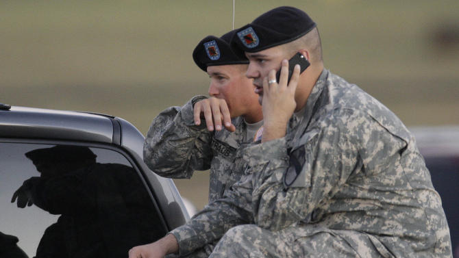 FILE - In this Thursday, Nov. 5, 2009 file photo, Spc. Ryan Howard of Niles, Mich., right and Spc. David Straub of Ardmore, Okla. wait for news of fellow soldiers while waiting at the gate of the Army base after a shooting at Fort Hood, Texas. (AP Photo/LM Otero)