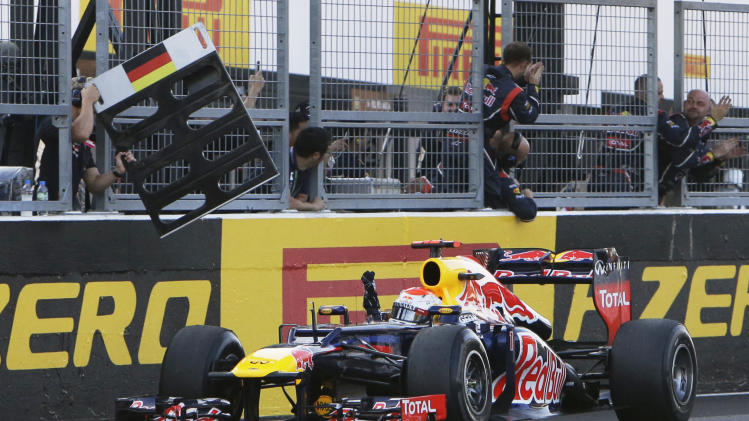 Red Bull driver Sebastian Vettel of Germany celebrates in front of his team after crossing the line to win the Japanese Formula One Grand Prix at the Suzuka Circuit in Suzuka, Japan, Sunday, Oct. 7, 2012. (AP Photo/Greg Baker)