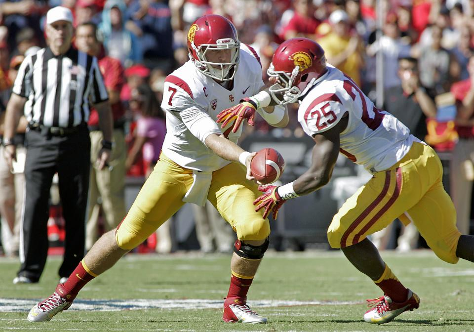 Southern California's starting quarterback Matt Barkley (7) hands the ball off to Silas Redd (25) in the backfield during the first half of an NCAA college football game against Arizona in Tucson, Ariz., Saturday, Oct. 27, 2012. (AP Photo/John Miller)