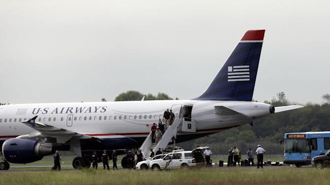 """Passengers walk off a US Airways flight at Philadelphia International Airport, after the plane returned to the airport, Thursday, Sept. 6, 2012, in Philadelphia. Airport spokeswoman Victoria Lupica says US Airways Flight 1267 returned to the airport Thursday morning as a """"precaution.""""   Footage from WCAU-TV showed a person being escorted off the plane by law enforcement officials and police dogs on the tarmac. An FBI spokesman did not immediately comment on the situation.(AP Photo/Matt Rourke)"""
