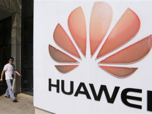 File photo of a man walking past a Huawei company logo outside the entrance of a Huawei office in Wuhan