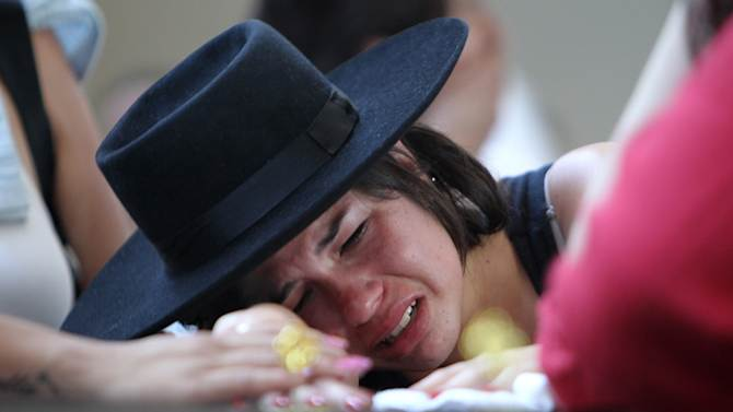 A woman cries over the coffin of a victim at a gymnasium where bodies were brought for identification in Santa Maria city, Rio Grande do Sul state, Brazil, Sunday, Jan. 27, 2013. Flames raced through a crowded nightclub in southern Brazil early Sunday, killing more than 230 people as panicked partygoers gasped for breath in the smoke-filled air, stampeding toward a single exit partially blocked by those already dead. (AP Photo/Nabor Goulart)